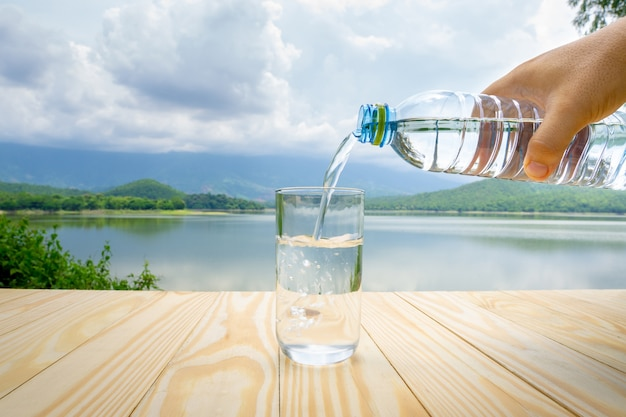 Passe segurar, água, garrafa plástica, e, despejar, um, vidro, ligado, tabela madeira, com, lago