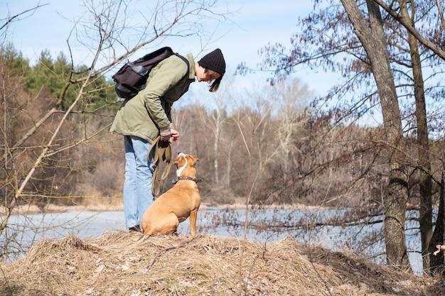 Passear e ensinar o cão em estado selvagem. mulher se comunicando com seu cachorro na floresta à beira do rio, estilo casual e caminhadas