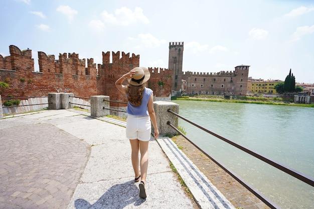 Passeio à beira-rio em verona, itália. bela dama, caminhando ao longo do calçadão com a fortaleza medieval, o castelo de castelvecchio e a ponte ao fundo.