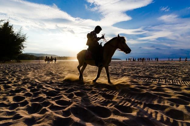 Passeio a cavalo na praia ao pôr do sol