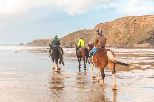 Passeio a cavalo na praia no país de gales ao pôr do sol