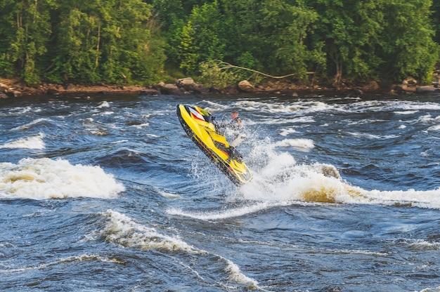 Passeio acrobático em um jet ski em um rio agitado luz natural