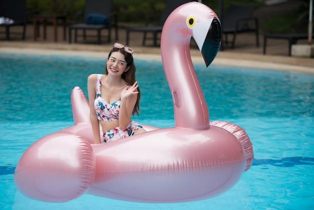 Passeio asiático novo da mulher no flamingo inflável gigante na piscina.