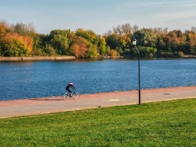 Passeio de bicicleta ao longo do aterro ao longo do rio.