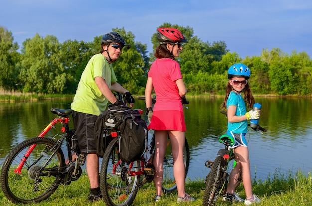 Passeio de bicicleta em família ao ar livre, pais ativos e criança andando de bicicleta e relaxando perto do belo rio