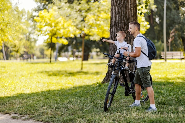 Passeio de bicicleta em família. pai e filho fazem uma pausa do ciclismo em um parque verde em um dia ensolarado de verão. uma criança com boné está sentada em uma cesta e apontando para algo enquanto o homem está de pé