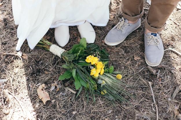 Passeio de casamento na floresta de pinheiros. dia ensolarado. casal de noivos na floresta. linda noiva e noivo em uma caminhada. vestido de noiva branco. bouquet de peônias e hortênsias.