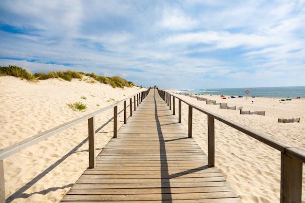 Passeio de madeira sobre dunas de areia na praia perto do oceano atlântico em portugal