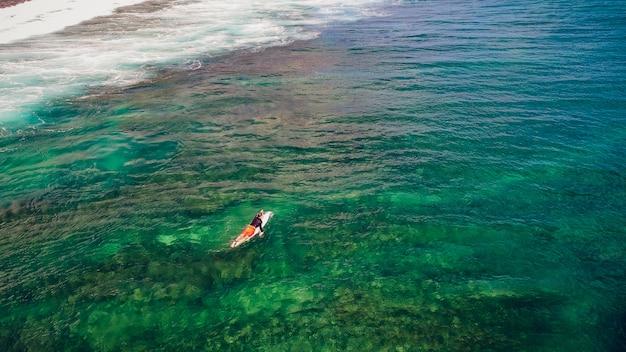 Passeio de surfista nas ondas no pôr do sol do oceano, vista superior