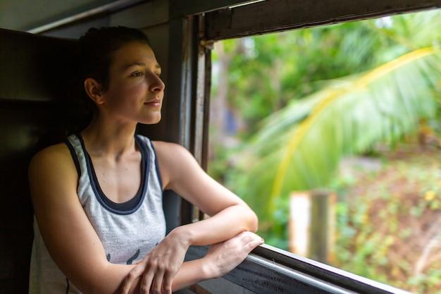 Passeio de trem no sri lanka. mulher sentada e olhando pela janela