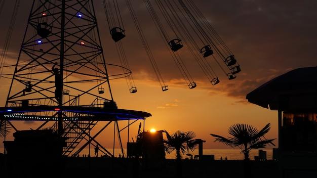 Passeio em cadeia de rotatória de carrossel giratório ao pôr do sol. entretenimento na praia, silhuetas de palmeiras em um fundo de mar pôr do sol