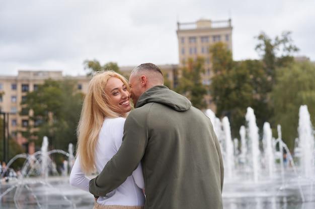 Passeio romântico. jovem casal apaixonado se abraçando perto de uma fonte no parque urbano, homem sussurrando elogios para a linda namorada