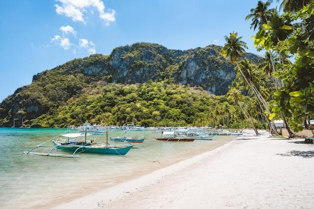Passeio turístico em barcos de banca na bela praia de corong corong, el nido. palawan, filipinas. verão