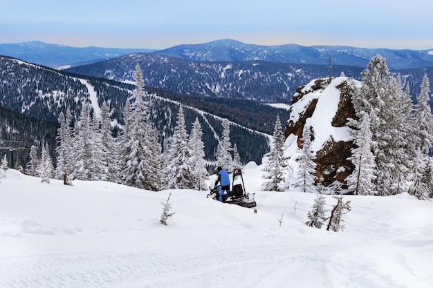 Passeios de moto de neve na montanha coberta de neve.