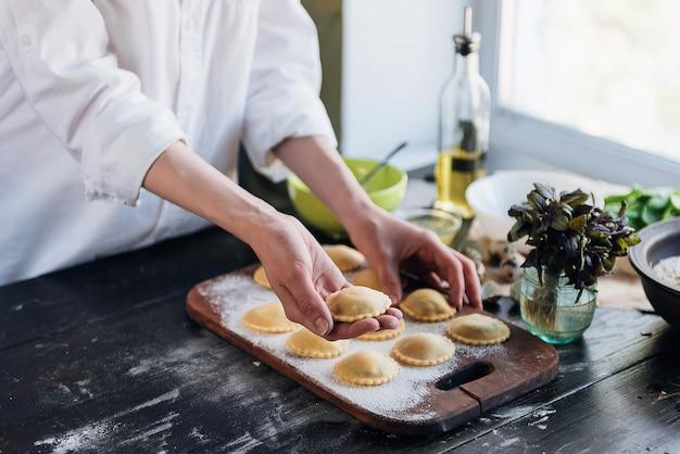Passo a passo, o chef prepara ravioli com queijo ricota, gemas de ovos de codorna e espinafre com especiarias. o chef prepara-se para cozinhar ravioli