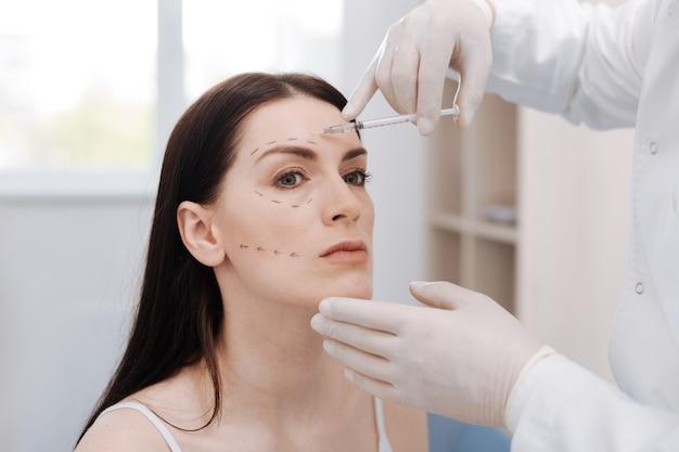 Passo arriscado. mulher elegante e carismática incrível sentada no consultório médico enquanto ele injeta botox em sua pele para melhorar suas características
