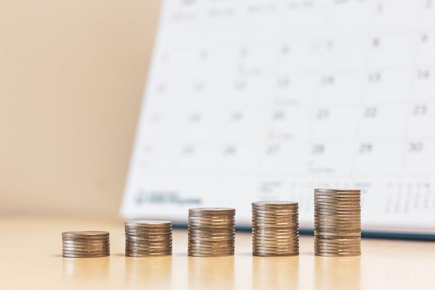 Passo de dinheiro moedas pilhas com fundo de calendário passo de dinheiro moedas pilhas com fundo de calendário