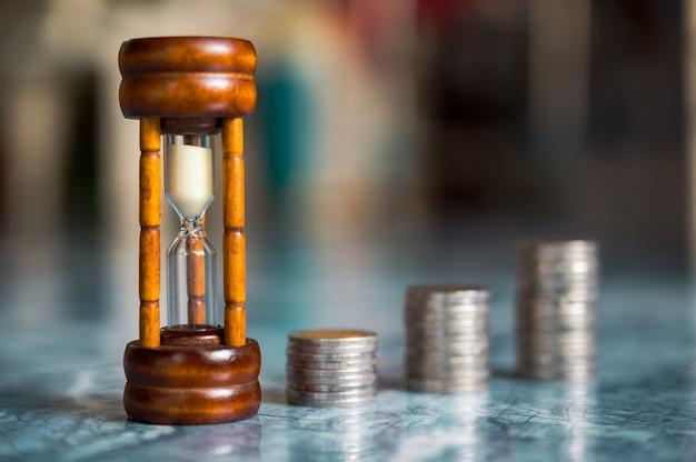 Passo de pilhas de moedas com ampulheta ou ampulheta, poupança e investimento ou conceito de planejamento familiar