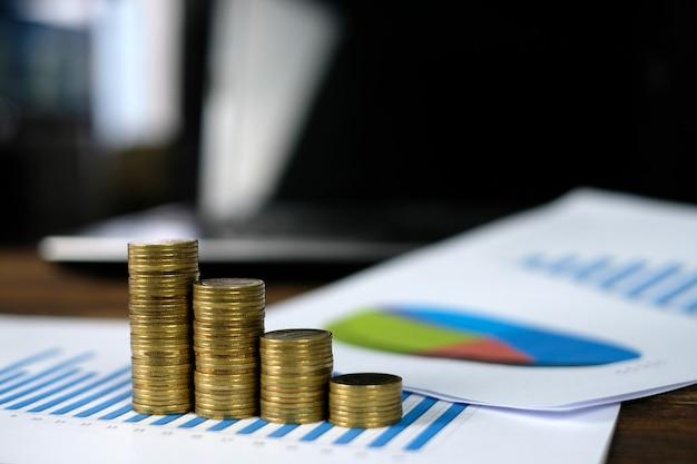 Passo de pilhas de moedas com computador portátil notebook e gráfico financeiro em papel branco na mesa de trabalho