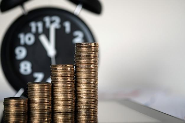 Passo de pilhas de moedas e despertador com computador tablet