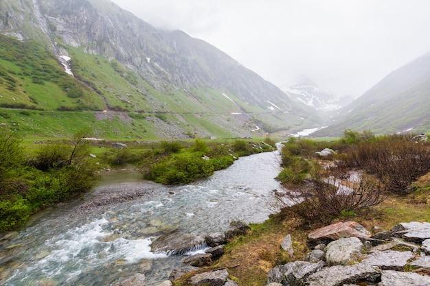 Passo del san gottardo ou st. gotthard pass verão paisagem enevoada com fluxo de água (suíça). tempo chuvoso.