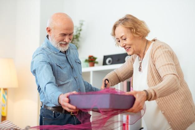 Passo final. mulher simpática e alegre cortando a fita com uma tesoura enquanto termina de embrulhar o presente