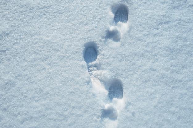 Passos na neve. textura para o fundo de natal Foto Premium