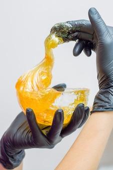 Pasta de açúcar ou mel de cera para remoção de pêlos com luvas pretas mãos de cosmetologista em salão de spa