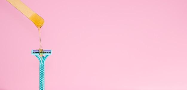 Pasta de açúcar para depilação com lâmina. a pasta de adoçante pinga em uma navalha em um fundo rosa, copyspace. o conceito de depilação, spa, cuidados com o corpo.