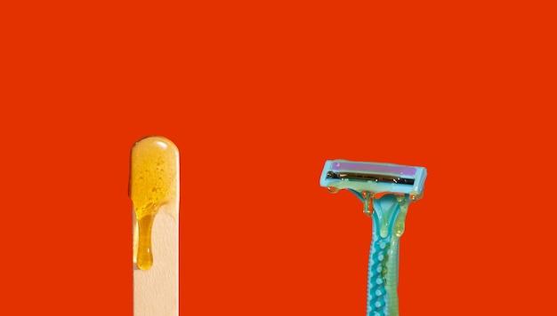 Pasta de açúcar para depilação com lâmina. shugaring paste em uma espátula de madeira. o conceito de depilação, spa, cuidados com o corpo.