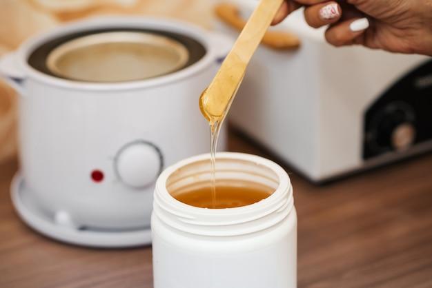 Pasta de açúcar quente natural para depilação em uma jarra e uma espátula de madeira nas mãos de uma esteticista de mulher