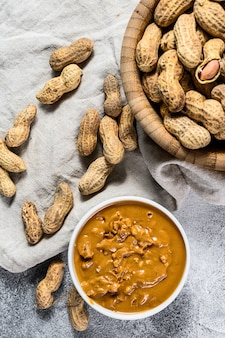 Pasta de amendoim em uma tigela, amendoim cru, comida vegetariana, vista superior
