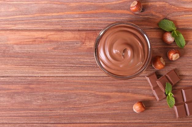Pasta de chocolate em uma jarra de vidro em um fundo colorido
