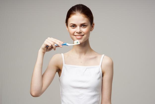 Pasta de dente linda mulher escovando os dentes estúdio de saúde bucal estilo de vida