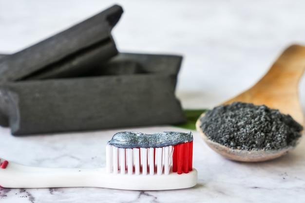 Pasta de dente por pó de carvão ativado na mesa de mármore