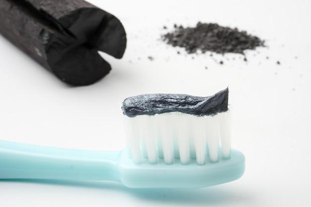 Pasta de dentes pelo pó de carvão ativado no fundo branco