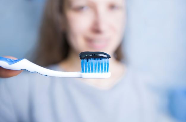 Pasta de dentes preta, feita de carvão ativado em uma escova,