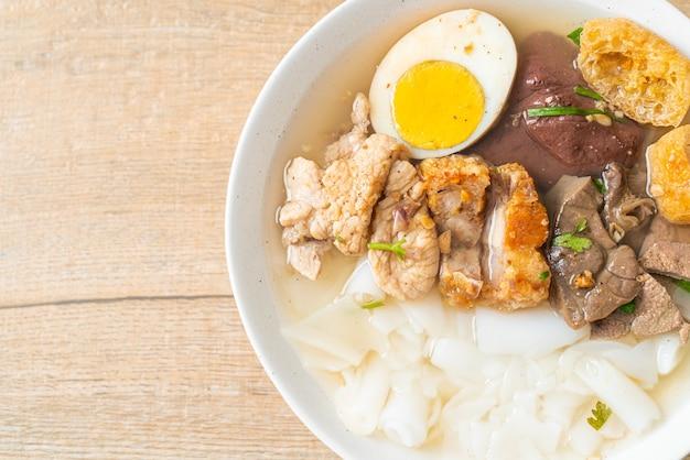 Pasta de farinha de arroz ou massa chinesa cozida quadrada com carne de porco em sopa clara - estilo de comida asiática