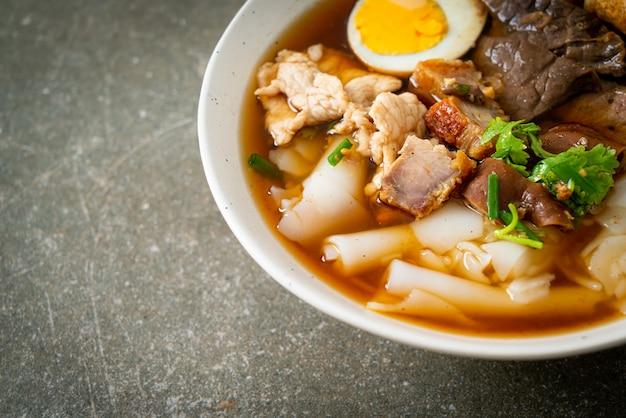 Pasta de farinha de arroz ou massa chinesa cozida quadrada com carne de porco na sopa marrom - estilo de comida asiática