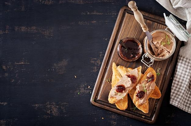 Pasta de fígado caseiro de frango ou patê em frasco de vidro com torradas e geléia de mirtilo com pimentão.