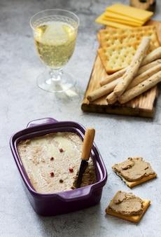 Pasta de fígado de frango, cebola e cenoura, servida com bolachas, grissini e champanhe.
