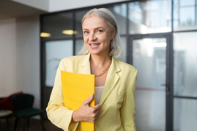Pasta de papel. closeup retrato de uma mulher de negócios bonita com uma jaqueta amarelo-clara segurando uma pasta de papel e olhando para a câmera