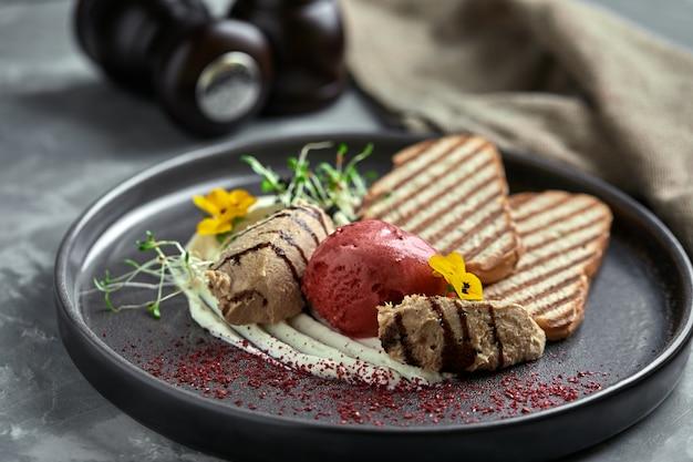 Pasta de pato com sorvete e croutons de pão branco grelhado. close-up, chave baixa, cinza.