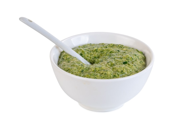 Pasta de pimenta malagueta picante. molho verde na tigela de cerâmica isolado no branco