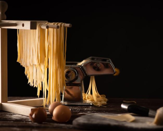 Pasta de tagliatelle preparada na hora é seca em um secador de madeira, cozinha italiana tradicional