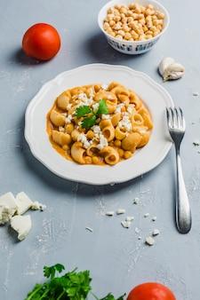 Pasta pipa o rigat com molho de grão de bico e tomate, polvilhado com queijo feta e coentro