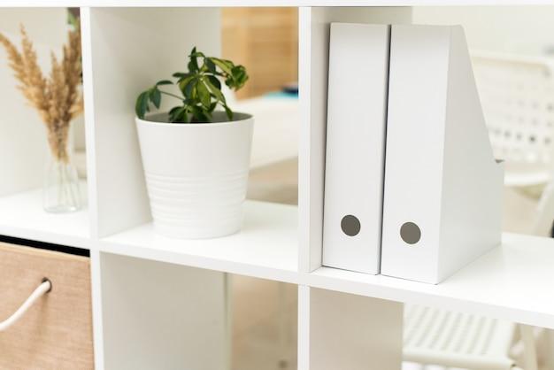 Pastas brancas para documentos, plantas no escritório e caixas em um armário aberto de trabalho. imagem da placa com documentos no escritório.