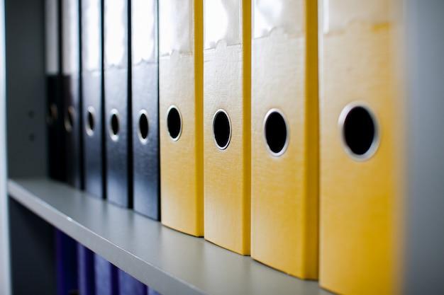 Pastas de arquivo coloridas para documentos nas prateleiras do escritório