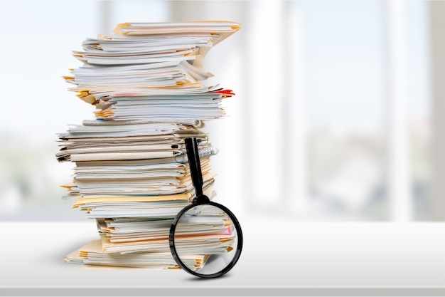 Pastas de arquivos com documentos e lupa no fundo
