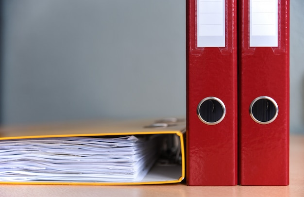 Pastas de cor grande para documentos sobre a mesa no escritório, close-up, copie o espaço